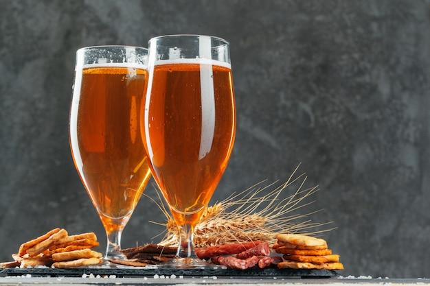 ブレッツェルと乾燥ソーセージスナックとビールのグラスをクローズアップ