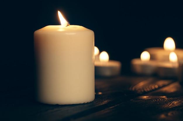 黒の上の暗闇の中で燃えているキャンドル。記念コンセプト。