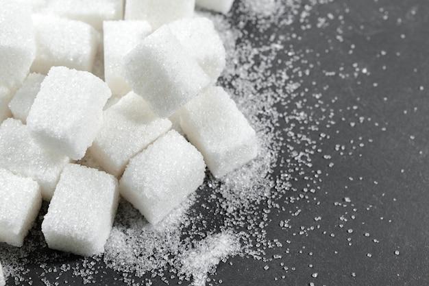 黒の上の白い砂糖キューブをクローズアップ