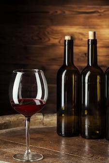 ボトルと木製樽で赤ワインのグラスは暗い木製で撮影