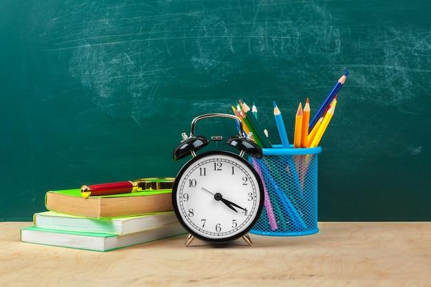 学用品。筆記用具と目覚まし時計。勉強する時間