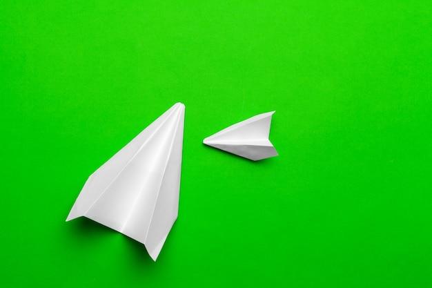 Белый бумажный самолетик на зеленой бумаге