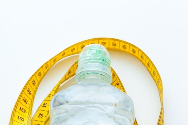 健康的な生活のためのボトル入りの水と白で測定テープ