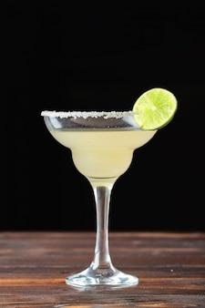 暗い背景においしいアルコールカクテルのグラス