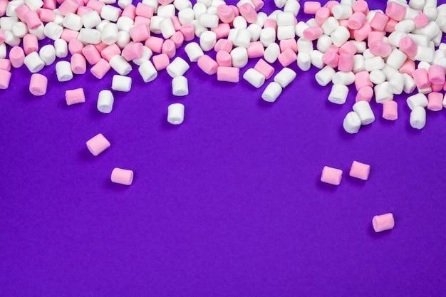 紫色の紙の背景に広げてマシュマロ