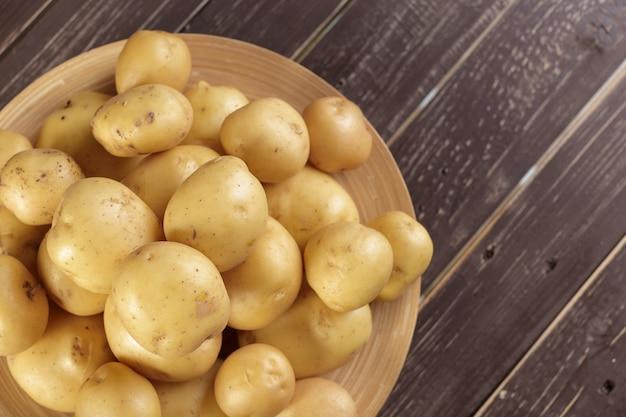 Свежий картофель на фоне дерева