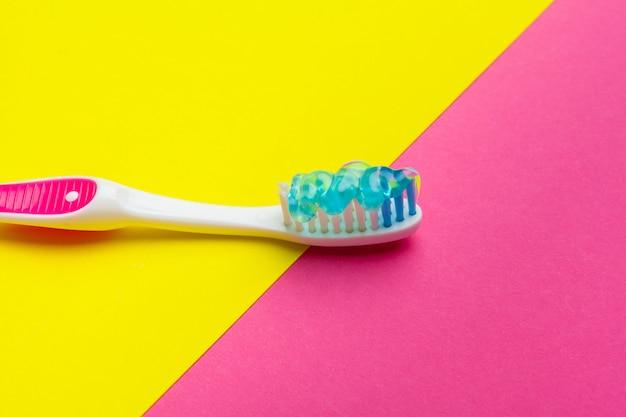 色の背景に手動歯ブラシでフラットレイアウト構成