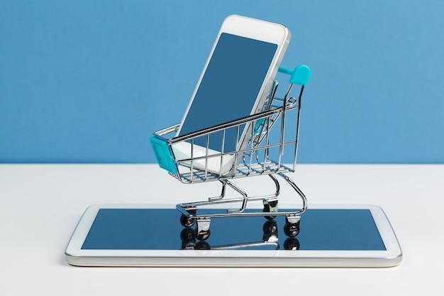 白い背景の上のショッピングカートを持つスマートフォン