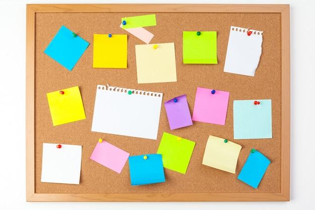ピン付きのいくつかのカラフルな空白ノートとコルク板