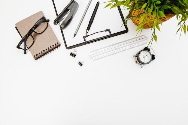 白いテーブルに事務用品を使用してクリップボード