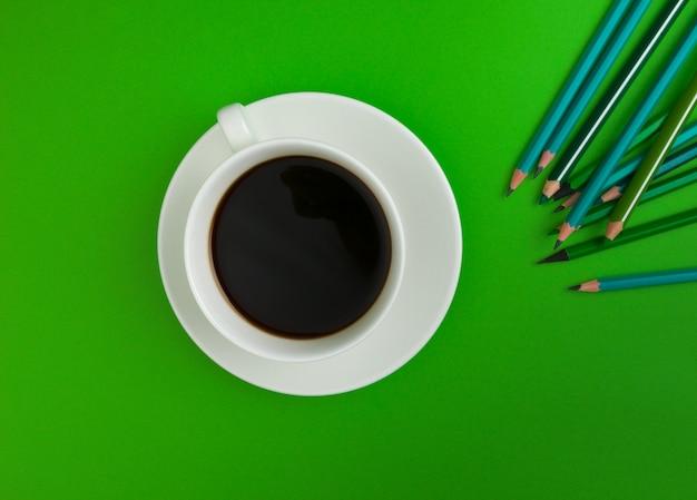 Куча карандашей на ярко-зеленом фоне