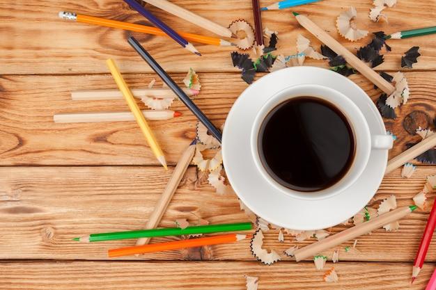 Кофейная чашка с карандашами и порезы карандашом на деревянном фоне