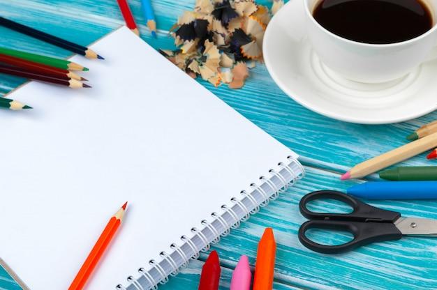 木製の背景に鉛筆と鉛筆カットでコーヒーカップ