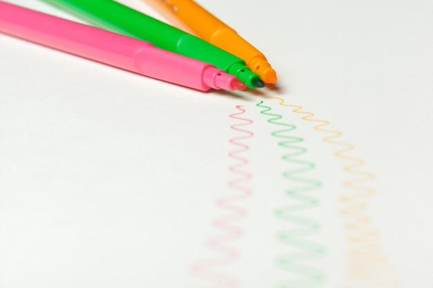 Фломастеры с нарисованными цветными метками на белом фоне