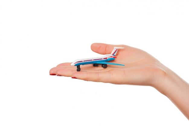 白い背景で隔離のおもちゃの飛行機を持っている女性の手