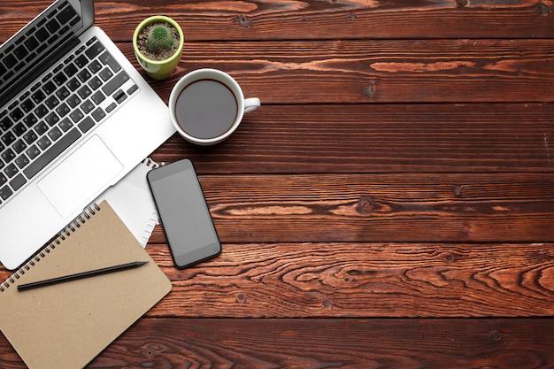 暗い木製のテーブル、トップビューで事務用品や機器
