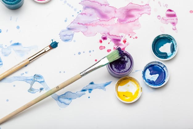 水彩絵の具の飛沫と絵画用品をクローズアップ