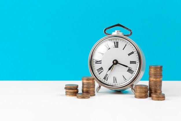 テーブルの上の目覚まし時計とお金のコイン。