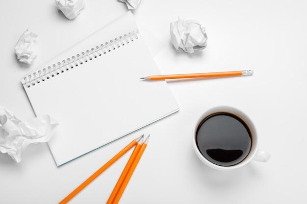 ビジネスの創造性の概念。コーヒー、紙のシート、テーブルの上のしわくちゃの札束