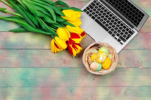 イースターエッグ、モックアップノートパソコン、チューリップの花束。