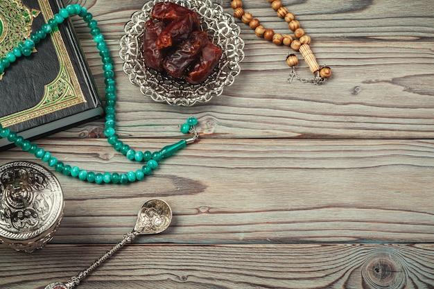 ロザリオとコーランの聖典とのデートのテーブルトップ装飾ラマダンカリーム休日