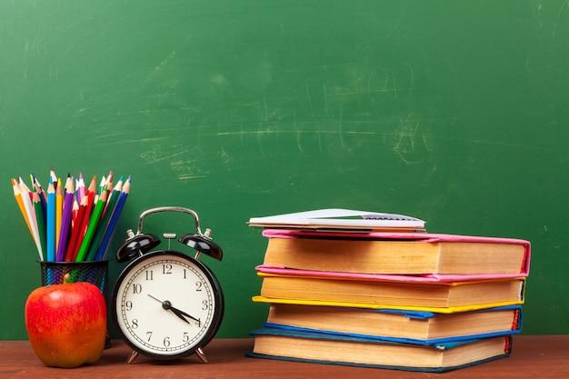 机の上の本、紙、鉛筆の山の上の赤いリンゴ