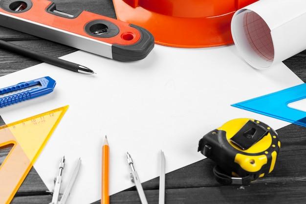 オレンジ色のヘルメットと木製の真ん中にコピースペースを持つさまざまな修復ツールを閉じる