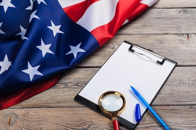 空白のクリップボードと木製の米国旗