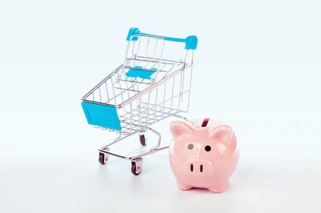 貯金箱と白で隔離される空のショッピングカート