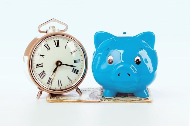 お金の山の時計と貯金箱。