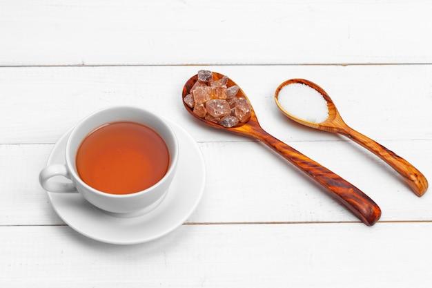 テーブルの上の砂糖と熱いお茶のガラスカップ