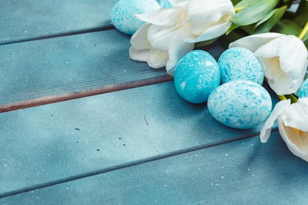 青い木製の背景にチューリップとイースターエッグ
