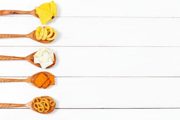 スナックのミックス:テーブルの上のプレッツェル、クラッカー、チップス、ナチョス