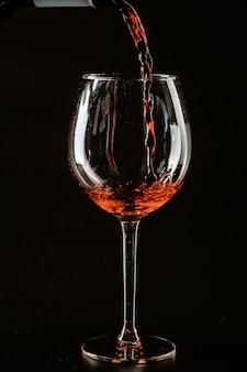 Красное вино наливают в бокал на темном