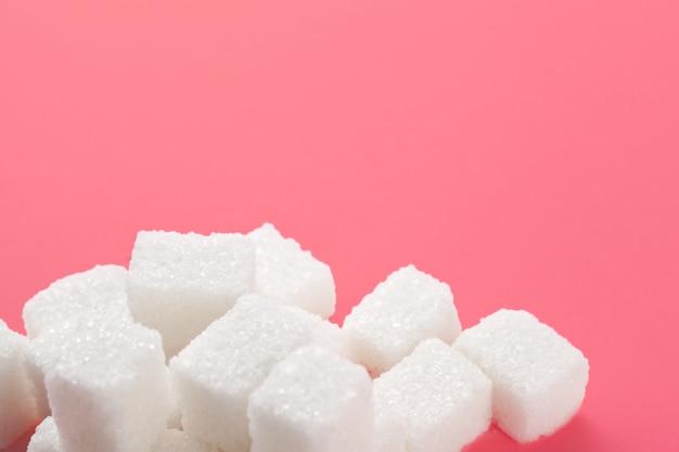 ピンクの背景に砂糖のキューブ。