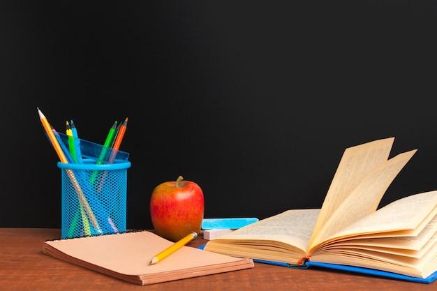 学校概念に戻る。本と木製の机の上のリンゴと黒板