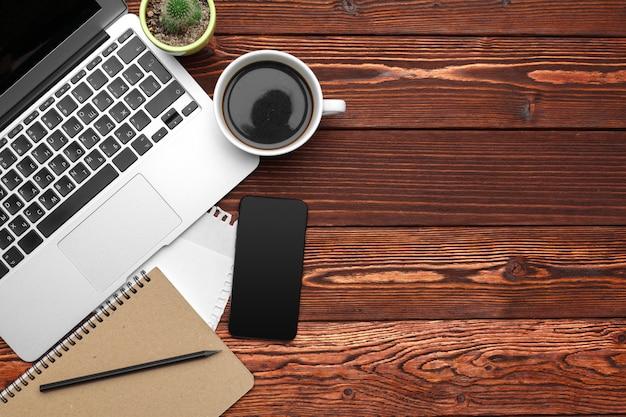 事務用品および暗い木製のテーブルの機器