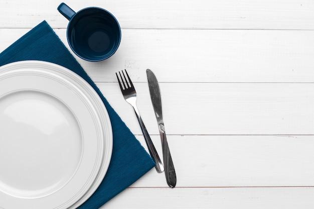 Пустая тарелка и полотенце на деревянный стол