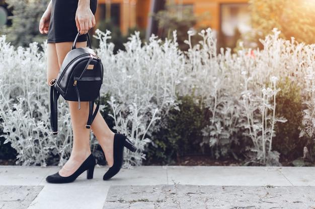 女性が通りでポーズ、暗いバッグを保持