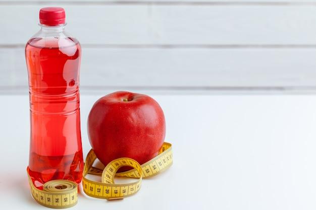 水のボトル、測定テープ、テーブルの上の新鮮なリンゴ
