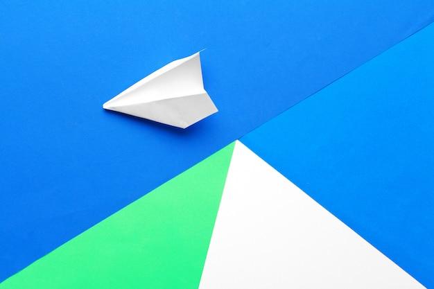 パステルブルーの背景に白い紙飛行機と白紙のフラットレイアウト
