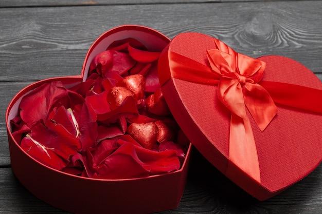 Много лепестков роз внутри открытой подарочной коробки на старом дереве, сладкий праздник с лепестками роз