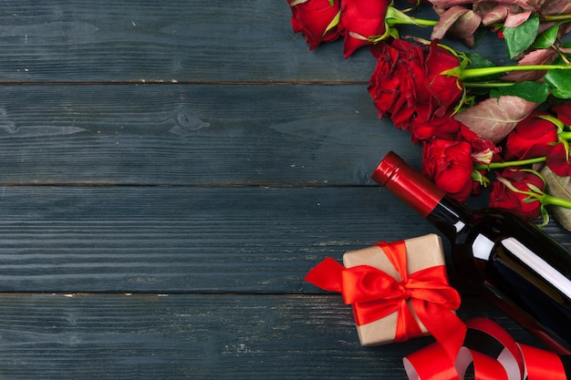 Поздравительная открытка дня валентинок, цветки красной розы, вино и подарочная коробка на деревянном столе.