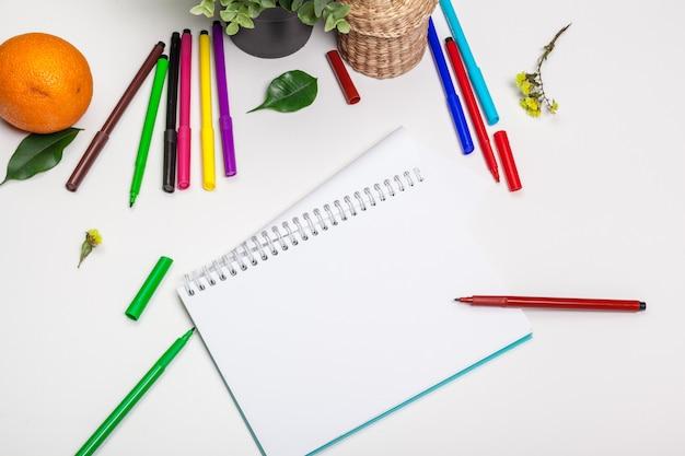 さまざまな色のフェルトチップマーカーとテキスト用のスペースを持つ空白のスケッチブックのセット