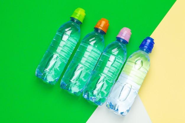 テーブルの上の異なる色のキャップが付いているプラスチック製の水ボトル