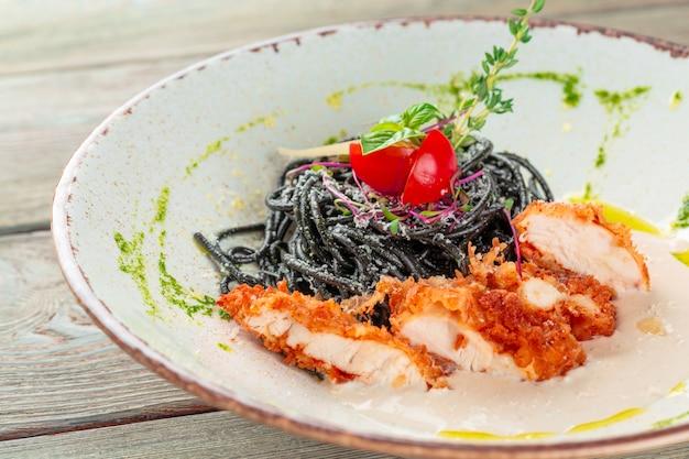 ルッコラとトマトのハーブで鶏肉と新鮮な黒のタリオリーニパスタ
