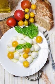 黄色のトマトとバジルの新鮮なモッツァレラチーズ。
