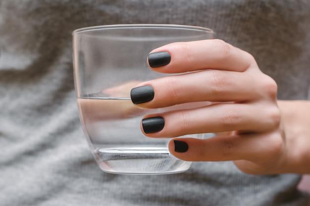 黒マットネイルデザインの女性の手。