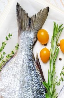 Сырая рыба дорадо с травами, приготовленными для приготовления пищи.