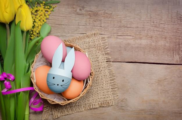 Пасхальные яйца и желтые тюльпаны на деревянном фоне